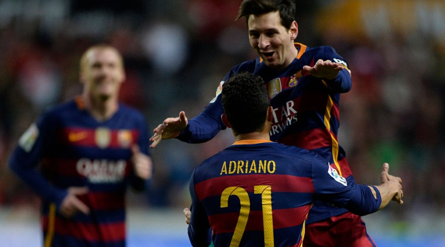 Barcelona's Argentinian forward Lionel Messi celebrates with teammate Brazilian defender Adriano after scoring a goal during the Spanish league football match Real Sporting de Gijon vs FC Barcelona at El Molinon stadium in Gijon on February 17, 2016. / AFP / MIGUEL RIOPA        (Photo credit should read MIGUEL RIOPA/AFP/Getty Images)
