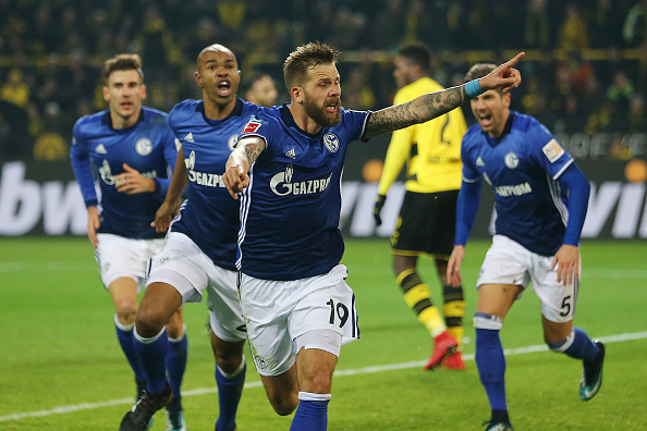 DORTMUND, GERMANY - NOVEMBER 25: Guido Burgstaller of Schalke (19) celebrates after Naldo of Schalke (left behind him) scored a goal to make it 4:4 during the Bundesliga match between Borussia Dortmund and FC Schalke 04 at Signal Iduna Park on November 25, 2017 in Dortmund, Germany. (Photo by Christof Koepsel/Bongarts/Getty Images)