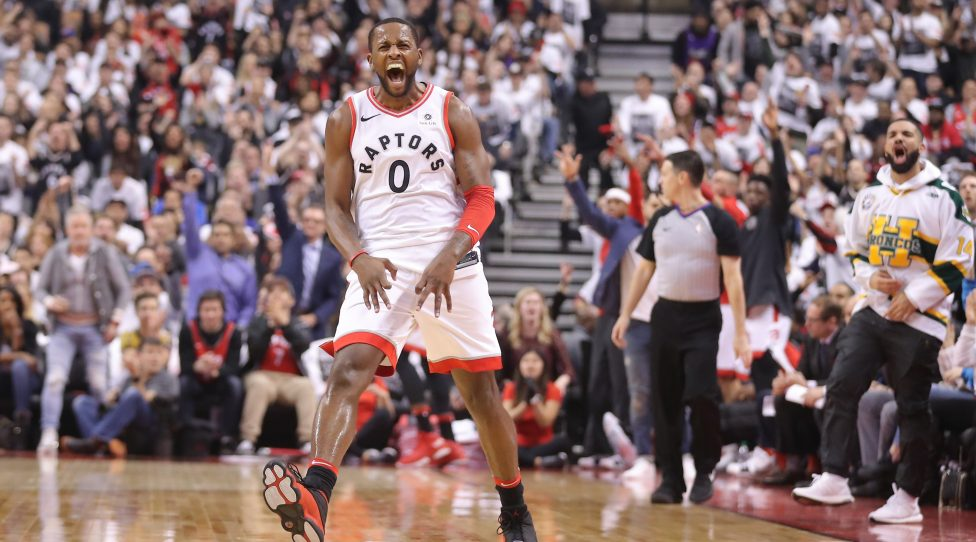 TORONTO, ON - APRIL 14: C.J. Miles #0 of the Toronto Raptors celebrates after making a three-pointer as rap artist Drake celebrates on the sideline against the Washington Wizards in the first quarter during Game One of the first round of the 2018 NBA Playoffs at Air Canada Centre on April 14, 2018 in Toronto, Canada. NOTE TO USER: User expressly acknowledges and agrees that, by downloading and or using this photograph, User is consenting to the terms and conditions of the Getty Images License Agreement. (Photo by Tom Szczerbowski/Getty Images)