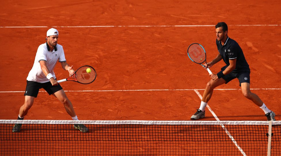 PARIS, FRANCE - JUNE 09:  Mate Pavic of Croatia and Oliver Marach of Austria return the ball during the mens doubles final against Pierre-Hugues Herbert of France and Nicolas Mahut of France during day fourteen of the 2018 French Open at Roland Garros on June 9, 2018 in Paris, France.  (Photo by Clive Brunskill/Getty Images)