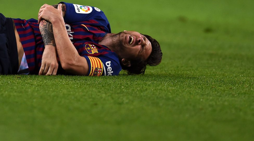 BARCELONA, SPAIN - OCTOBER 20: ionel Messi of FC Barcelona lies on the floor in pain after appearing to pick up an injury during the La Liga match between FC Barcelona and Sevilla FC at Camp Nou on October 20, 2018 in Barcelona, Spain. (Photo by Alex Caparros/Getty Images)