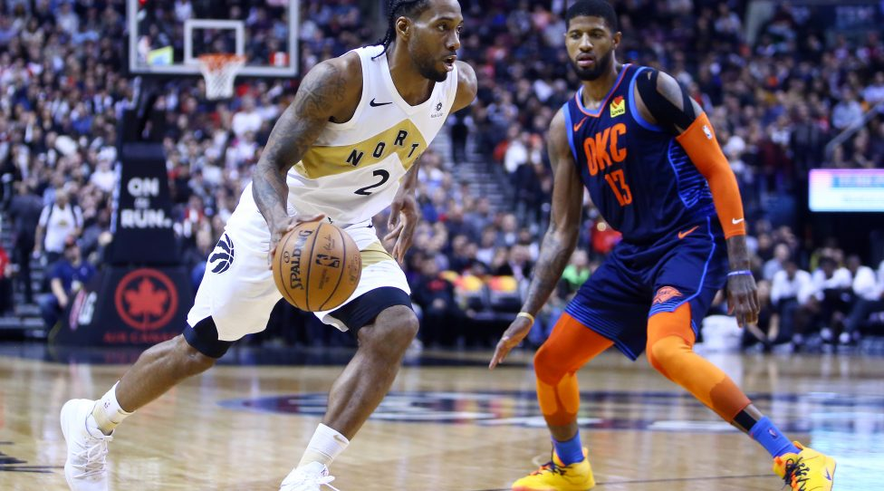 TORONTO, ON - MARCH 22:  Kawhi Leonard #2 of the Toronto Raptors dribbles the ball as Paul George #13 of the Oklahoma City Thunder defends during the second half of an NBA game at Scotiabank Arena on March 22, 2019 in Toronto, Canada.  NOTE TO USER: User expressly acknowledges and agrees that, by downloading and or using this photograph, User is consenting to the terms and conditions of the Getty Images License Agreement.  (Photo by Vaughn Ridley/Getty Images)