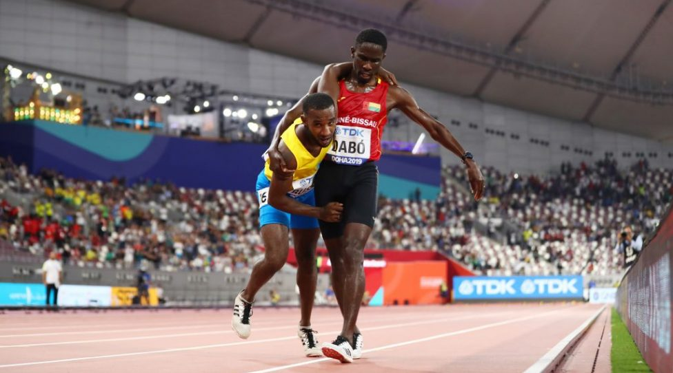 DOHA, QATAR - SEPTEMBER 27: Braima Suncar Dabo of Guinea-Bissau helps Jonathan Busby of Aruba reach the finish line in the Men's 5000 metres heats during day one of 17th IAAF World Athletics Championships Doha 2019 at Khalifa International Stadium on September 27, 2019 in Doha, Qatar. (Photo by Michael Steele/Getty Images)