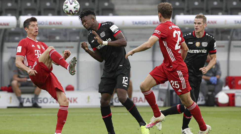BERLIN, GERMANY - JULY 04: Leverkusen's Edmond Tapsoba heads the ball between Bayern's Robert Lewandowski, left, and Bayern's Thomas Mueller  during the DFB Cup final match between Bayer 04 Leverkusen and FC Bayern Muenchen at Olympiastadion on July 4, 2020 in Berlin, Germany. (Photo by Michael Sohn/Pool via Getty Images)